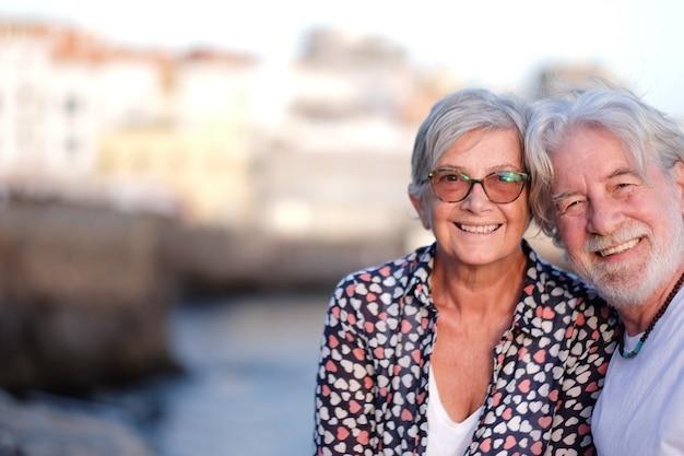 Schönes älteres paar, das im freien auf see bei sonnenuntergang lächelt und in die kamera schaut