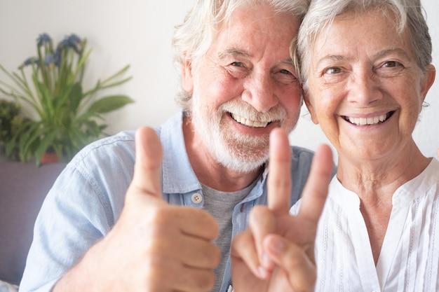 Schönes älteres paar, das in die kamera schaut und ein positives zeichen gestikuliert gelassene menschen, die den ruhestand genießen