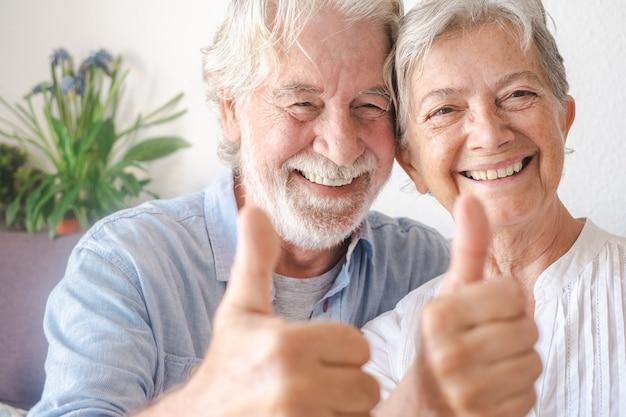 Schönes älteres paar, das in die kamera schaut und menschen mit positivem zeichen gestikuliert, die den ruhestand genießen