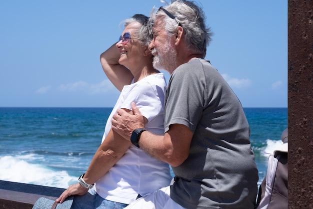 Schönes älteres paar, das nahe am meer sitzt und lächelnd wegschaut. zwei rentner genießen sommerferien und freiheit