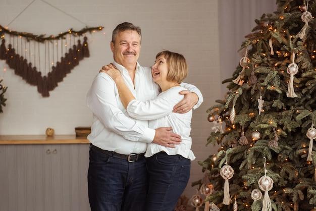 Schönes älteres paar, das spaß hat, während weihnachten zu hause steht, das durch weihnachtsbaum steht