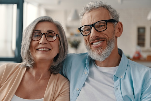 Schönes älteres paar in freizeitkleidung, das lächelt und in die kamera schaut, während es zeit zu hause verbringt