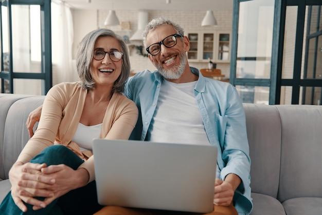 Schönes älteres paar in freizeitkleidung, das lächelt und laptop benutzt, während es zu hause zusammenhält?