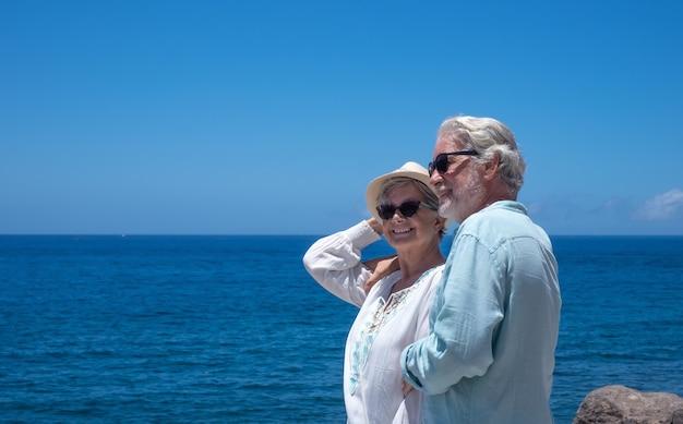 Schönes älteres paar umarmte sich vor dem meer. glückliche rentner, die am strand stehen und die sommerferien genießen