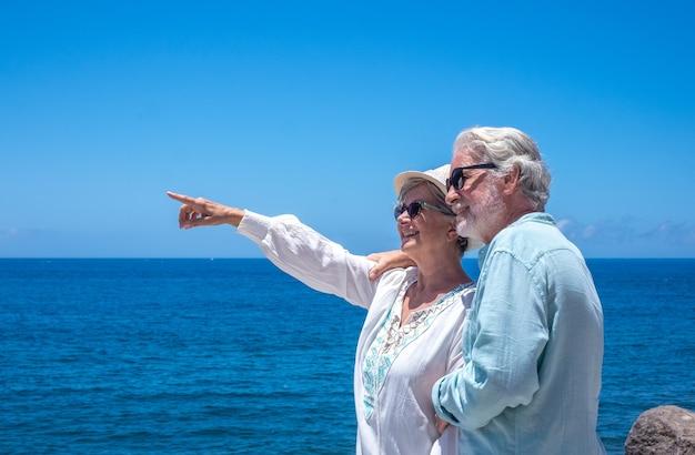 Schönes älteres paar umarmte sich vor dem meer und schaute weg. glückliche rentner, die am strand stehen und die sommerferien genießen