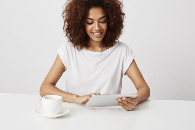 Schönes afrikanisches mädchen lächelnd, das tablette über weißer wand betrachtet. speicherplatz kopieren.