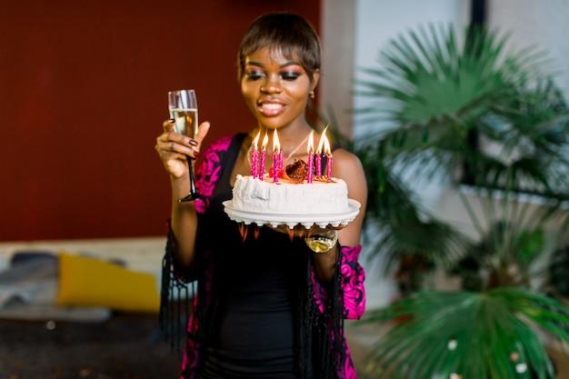 Schönes afrikanisches mädchen mit geburtstagstorte und mit kerzen und champagner anzünden
