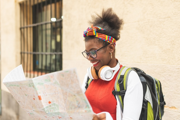 Schönes afroamerikanisches mädchen, das eine karte verwendet