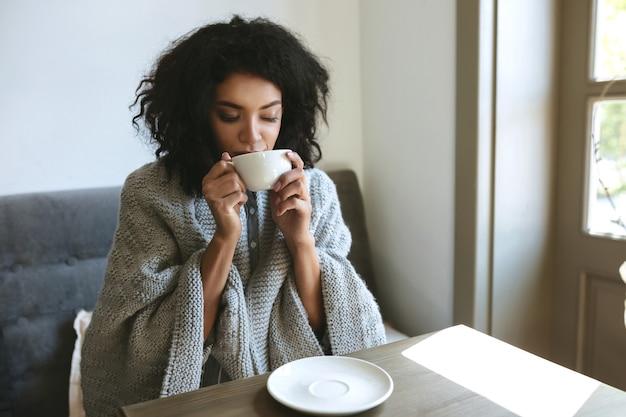 Schönes afroamerikanisches mädchen, das kaffee im restaurant trinkt. porträt der jungen dame mit dunklem lockigem haar, das verträumt ihre augen mit tasse in den händen schließt