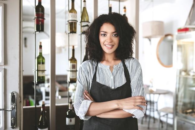 Schönes afroamerikanisches mädchen in der schürze, die mit den im restaurant gefalteten armen steht. junges mädchen mit dunklem lockigem haar, das in der schürze am café steht
