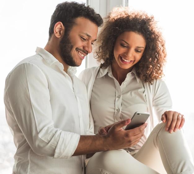 Schönes afroamerikanisches paar benutzt ein smartphone.