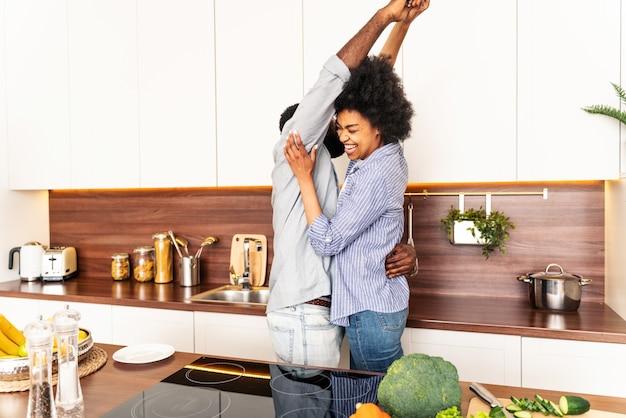 Schönes afroamerikanisches paar, das zu hause kocht