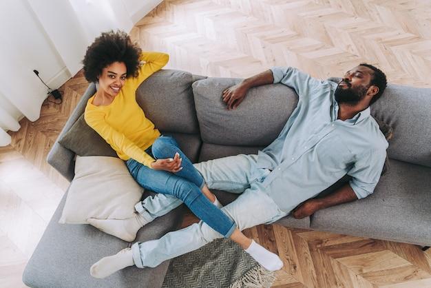 Schönes afroamerikanisches paar entspannt sich zu hause auf dem sofa - häusliches leben, fröhliche paarbindung und spaß im wohnzimmer