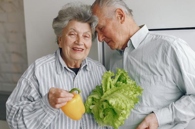Schönes altes ehepaar bereiten essen in einer küche zu