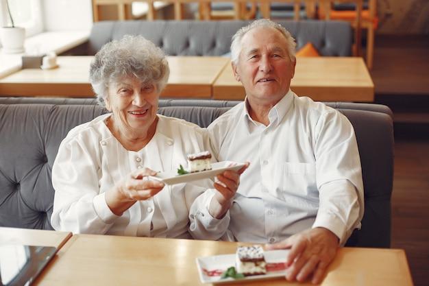 Schönes altes ehepaar, das in einem café sitzt