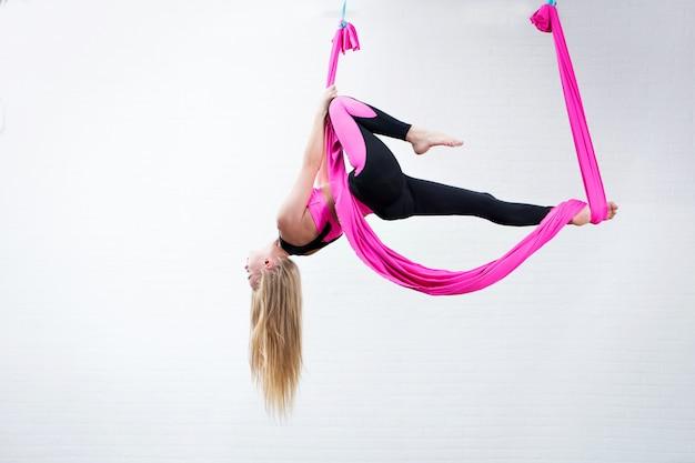 Schönes antigravitationsyoga des jungen mädchens auf einer rosa silk hängematte beim handeln.