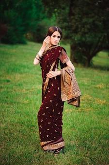 Schönes arabisches frauenporträt. junge hinduistische frau mit mehndi-tätowierungen vom schwarzen henna auf ihren händen