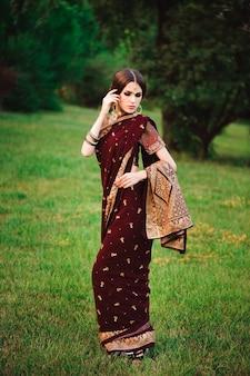 Schönes arabisches frauenporträt. junge hinduistische frau mit mehndi-tätowierungen vom schwarzen henna auf ihren händen.