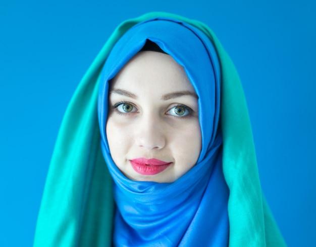 Schönes arabisches mädchen mit schal über blauem hintergrund