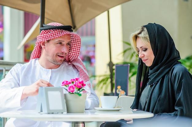 Schönes arabisches paar, das eine diskussion in einem vintagen interieur hat, arabisches paar, das über eine tasse kaffee in einem café spricht
