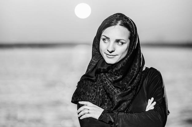 Schönes arabisches saudisches frauengesicht, das auf dem strand aufwirft