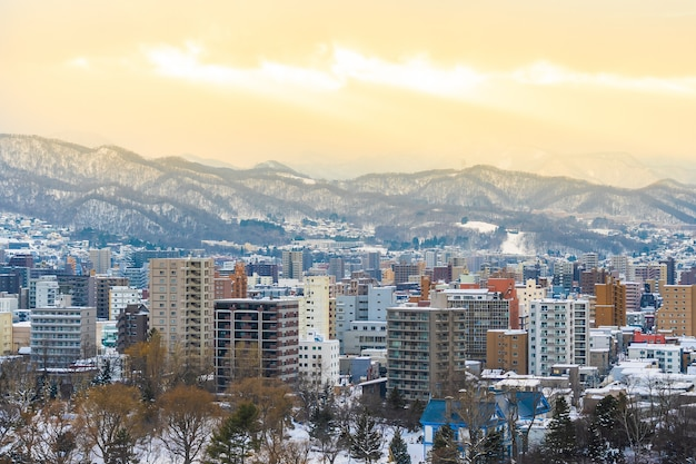 Schönes architekturgebäude mit berglandschaft in der wintersaison zur sonnenuntergangzeit