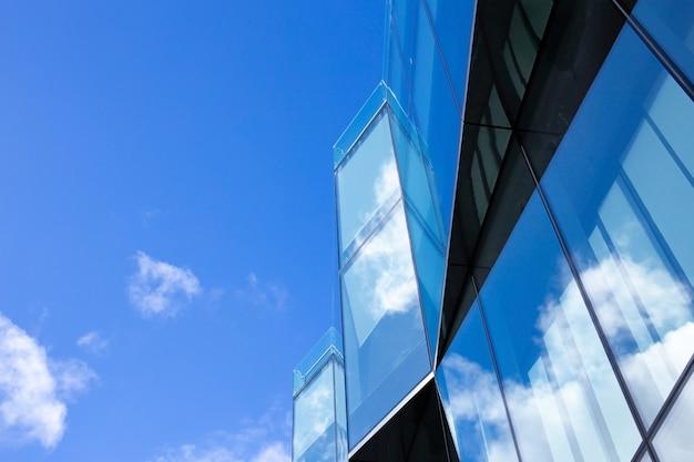 Schönes architekturgeschäftsbürogebäude mit fensterglasmuster in der wolkenkratzerstadt. wolken spiegeln sich in der glasfassade des gebäudes.