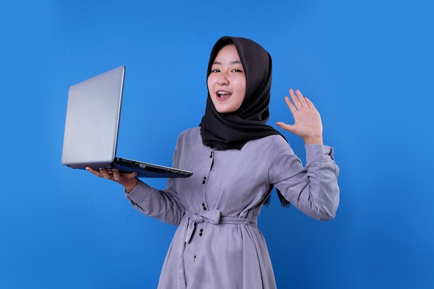 Schönes asiatisches frauenlächeln bringen einen laptop und schrie ausdruck