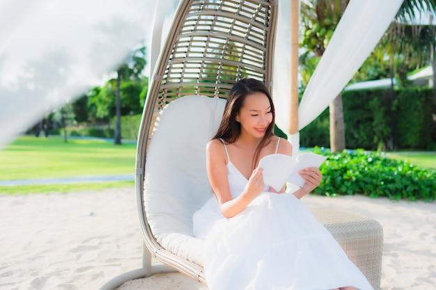 Schönes asiatisches frauenlesebuch des porträts um strandseeozean