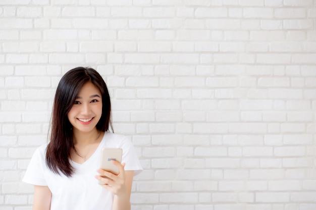 Schönes asiatisches frauennotelefon und -lächeln, die auf zementziegelsteinhintergrund stehen