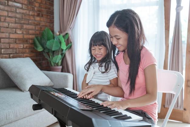 Schönes asiatisches jugendlich mädchen, das ein klavierinstrument spielt