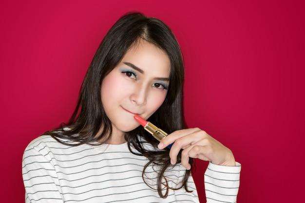 Schönes asiatisches junges brunettemädchen mit dem gelockten haar, das rosa lippenstift auf rosa hintergrund anwendet