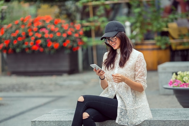 Schönes asiatisches junges frauenporträt unter verwendung des smartphones in der stadt