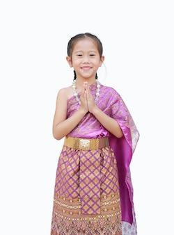 Schönes asiatisches kindermädchen im traditionellen thailändischen kleid, das lokal betet. (sawasdee bedeutet hallo).