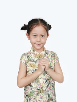 Schönes asiatisches kleines mädchen, das cheongsam mit lächelnder und willkommener geste trägt, die für glückliches chinesisches neujahr isoliert feiert