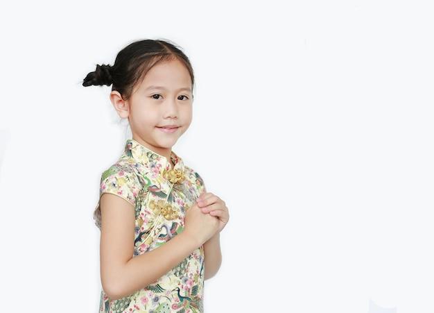Schönes asiatisches kleines mädchen, das cheongsam mit lächelnder und willkommener geste trägt, die für glückliches chinesisches neujahr lokalisiert auf weißem hintergrund feiert