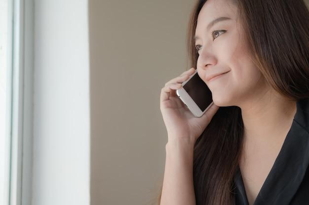Schönes asiatisches mädchen, das am intelligenten telefon mit smiley im büro spricht
