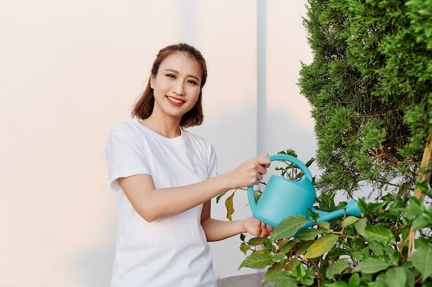 Schönes asiatisches mädchen, das die pflanzen gießt
