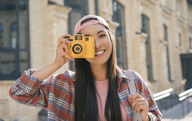 Schönes asiatisches mädchen, das foto auf retro-kamera macht