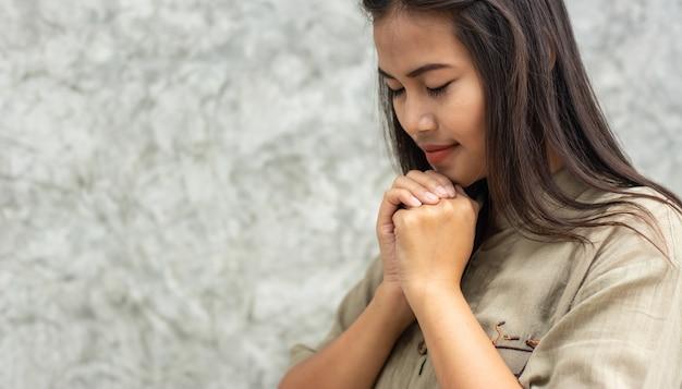 Schönes asiatisches mädchen, das für den segen gottes betend steht.