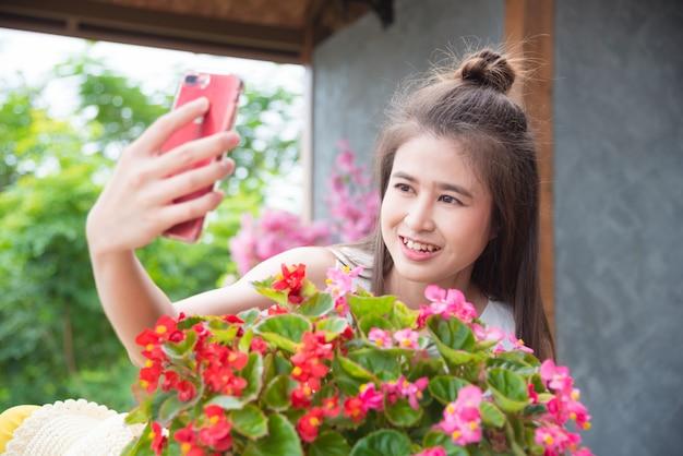 Schönes asiatisches mädchen, das ihr foto mit blumen durch intelligentes telefon macht
