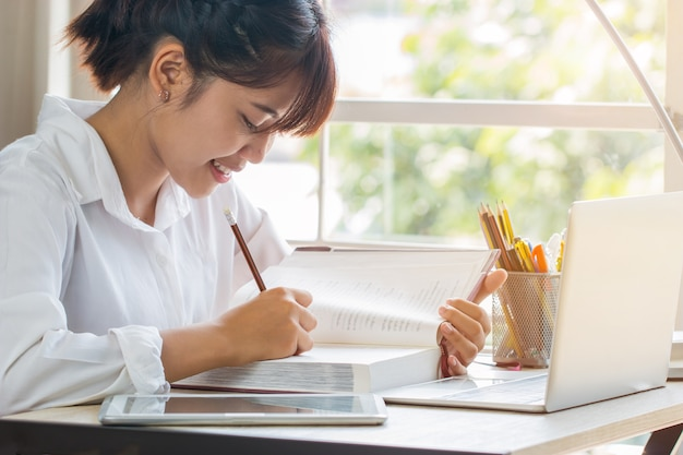 Schönes asiatisches mädchen, das im lehrbuch oder in der hausarbeit lernt und schreibt