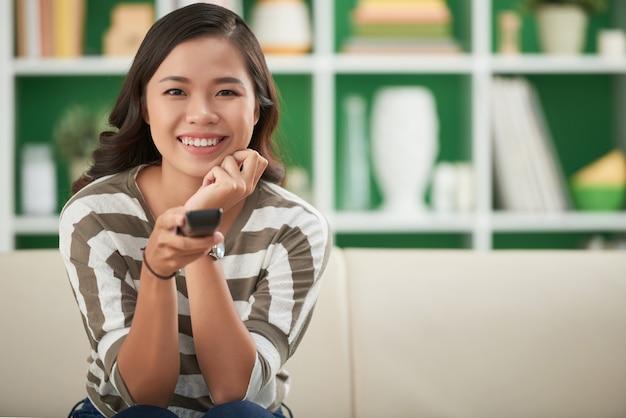 Schönes asiatisches mädchen, das zu hause auf couch sitzt und auf fernsehfernbedienung drückt