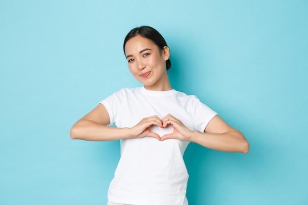 Schönes asiatisches mädchen im weißen t-shirt, das sympathie zeigt, sorgfalt und zärtliche gefühle gegenüber person ausdrückt, herzgeste zeigt und alberne stehende blaue wand lächelt