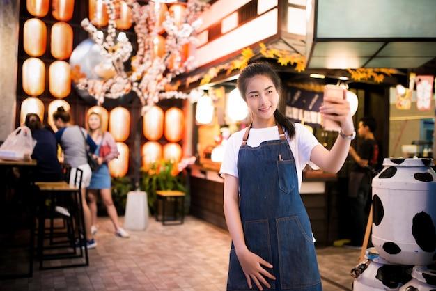 Schönes asiatisches mädchen macht ein foto im japanischen restaurant