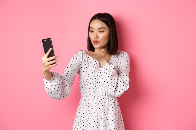 Schönes asiatisches mädchen mit fotofilter-app und selfie auf dem smartphone, posiert in süßem kleid vor rosa hintergrund