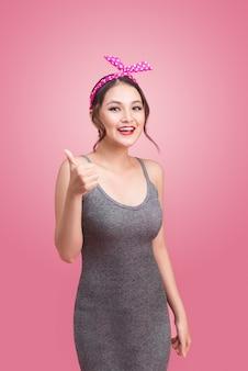 Schönes asiatisches mädchen mit hübschem lächeln im pinup-stil auf rosa hintergrund