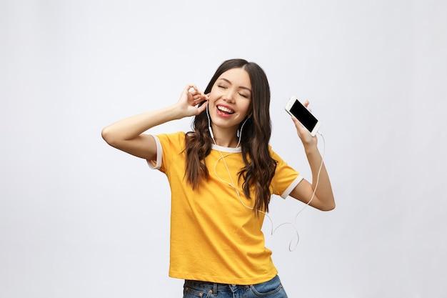Schönes asiatisches mädchen mit professionellem make-up und stilvoller frisur, die singend und tanzend, während musik hört