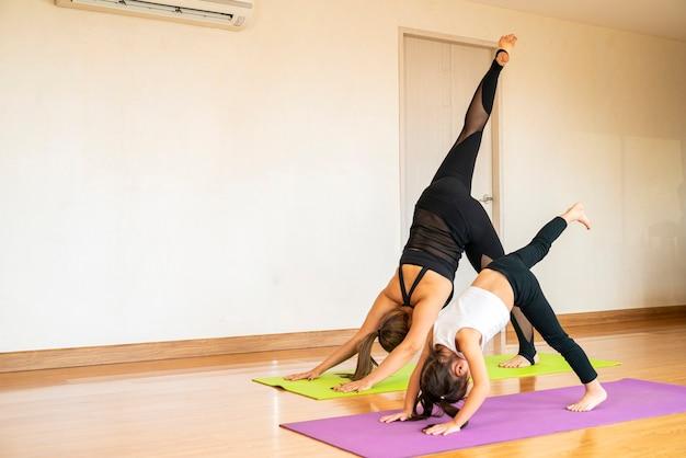 Schönes asiatisches mädchen und ihre mutter, die yoga macht, stellt trainingsübung zum entspannen und meditieren zu hause auf. asien, yoga, zen, sport, fitness. gesunde, häusliche aktivität oder asiatisches frauenkonzept