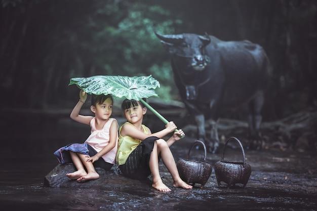 Schönes asiatisches mädchen zwei spielt das wasser im fluss bei thailand.